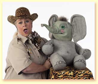 Photograph of Margaret Clauder as Masai Maggie, with the elephant puppet Sneezy, squirting her with water.