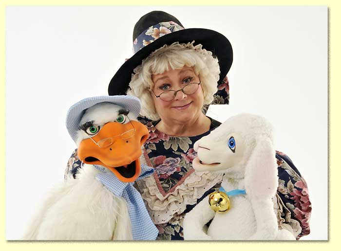 Photo of Mother Goose with a lamb puppet and a goose puppet.
